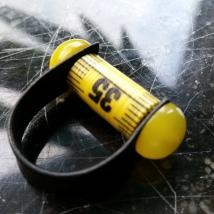 Måttbandsring med knappar och läderband, gul